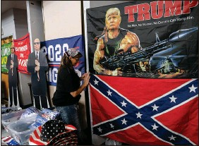 """?? CHRISTOPHER SMITH / THE NEW YORK TIMES ?? A woman pins a Confederate f lag to the wall during a gun show Sept. 3 in Osage Beach, Mo. The """"Second Amendment sanctuary"""" movement has gained new traction in the volatile post-trump era."""