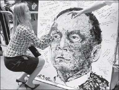?? Reuters photo ?? CHOICE WORDS FOR THE BOSS: Lehman Bros. employee Jennifer Roeder writes a message on a portrait of CEO Dick Fuld in on Monday.