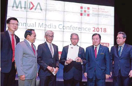 ?? PIC BY KHAIRUL AZHAR AHMAD. ?? International Trade and Industry Minister Datuk Seri Mustapa Mohamed (fourth from left) with Malaysia's Investment Performance Report 2017 at a press conference in Kuala Lumpur yesterday. With him are (from left) Deputy International Trade and Industry...