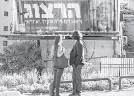 ?? Jack Guez / AFP/Getty Images ?? A campaign billboard rotates images of Prime Minister Benjamin Netanyahu, right, with his opponent, MP Labor Party leader Isaac Herzog, in Tel Aviv.