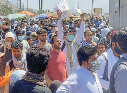 ?? /Reuters ?? Desperate: Crowds of people show their documents to US troops outside the airport in Kabul, Afghanistan. Warnings that blasts were expected had little effect in reducing the flood of people trying to flee the country via the airport.