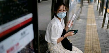 ?? Agence France-presse ?? ↑ A woman holding a mini electric fan waits at a bus stop in Beijing on Wednesday.