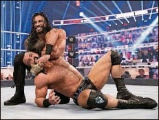 ?? WWE (2020) ?? SmackDown's universal champion Roman Reigns, left, and Raw's WWE champ Drew McIntyre wrestle at Survivor Series in November.