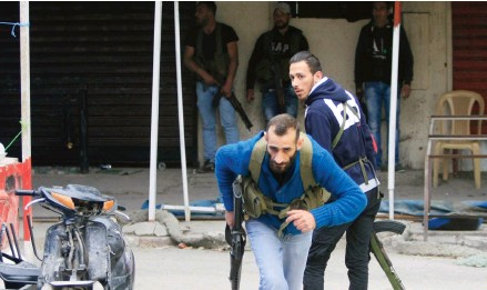 ??  ?? Gunmen run during clashes in Ain al-Hilweh between Fatah supporters and Islamist movements.