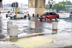?? PHOTOGRAPH: EUGENE COETZEE ?? GREAT LOSS: A burst pipe led to water running down Strand Street and pushing up the pavement yesterday