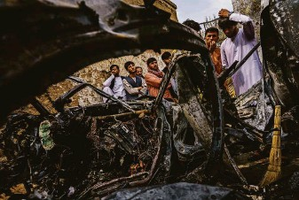 ?? Marcus Yam / Los Angeles Times ?? Relatives and neighbors of the Ahmadi family gathered around the incinerated Toyota Corolla that the family says was hit by a U.S. drone strike on Aug. 29 in Kabul, Afghanistan.