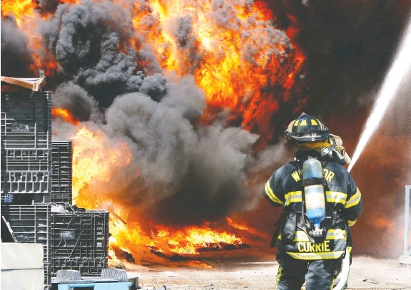 ?? SUPPLIED ?? Firefighter Wayne Currie, shown battling a blaze, says the job comes with many risks and health hazards. `We fight to ensure protections are in place,' he says.
