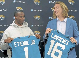 ?? Bob Self, The Florida Times-Union ?? Former Clemson teammates Travis Etienne and Trevor Lawrence pose with their Jacksonville Jaguars jerseys during a news conference after the NFL draft.