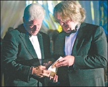 ?? CHUCK RUSSELL/VANCOUVER SUN ?? Former U.S. President Bill Clinton signs his book, My Life, for John Lefebvre, who bid thousands of dollars it at a Vancouver charity benefit last May. Lefebvre has been arrested in the U.S.