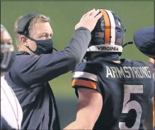 ?? ANDREWSHURTLEFF/THE DAILY PROGRESS ?? Virginia head coach BroncoMendenhall ( left) congratulated QB Brennan Armstrong during UVA's 44- 41 win over North Carolina. Armstrong threwfor three TDs and rushed for another in that game.