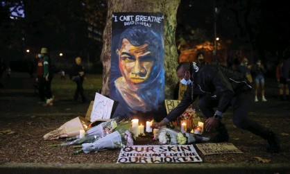 ?? Photograph: Anadolu Agency/Getty Images ?? A man places a candle beneath a portrait of David Dungay during a protest against Aboriginal deaths in custody in Sydney last year. A NSW inquiry into Aboriginal deaths in custody has recommended sweeping reforms to the justice system.