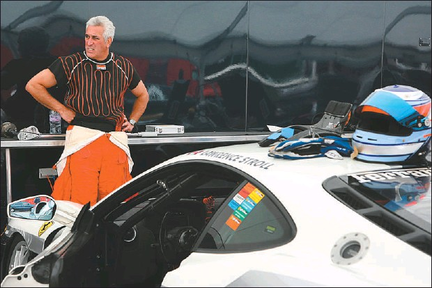 ?? ROGER LEMOYNE THE GAZETTE ?? Lawrence Stroll pauses by his race car during a Ferrari festival at the Circuit Mont Tremblant race track in July. Stroll is not only a racing fanatic, he's a wealthy fashion executive who revived the race track in 2000. But his enthusiasm for the...
