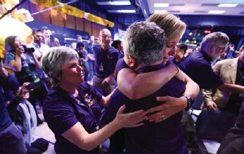 ?? ROBYN BECK/AFP/GETTY IMAGES ?? Cassini science team members in Pasadena, Calif., hug as the final loss of signal from the spacecraft is confirmed, indicating Cassini's destruction in Saturn's atmosphere and the end of its 20-year mission.
