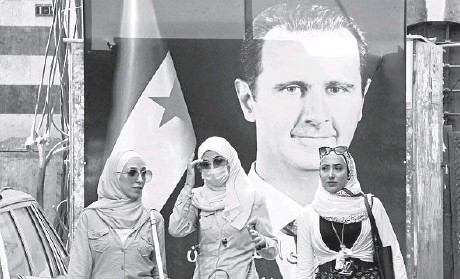 ?? LOUAI BESHARA/GETTY-AFP ?? Syrians walk in front of a poster of President Bashar Assad last month near the Grand Umayyad Mosque in Damascus.