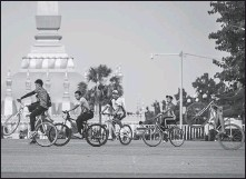 ??  ?? Left: Residents cycle in downtown Vientiane, capital of Laos.