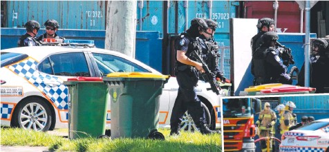 ??  ?? Police ready to react at the seige on Finucane Rd near Abelia St, Capalaba, while fire and emergency services wait. Pictures: David Clark