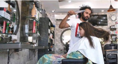 ?? File / Agence France-presse ?? ↑ Ali Abbas uses a butcher knife to cut the hair of a customer at his shop in Lahore.