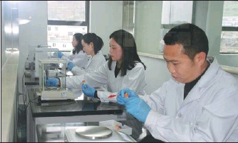 ?? WANG JIN / CHINA DAILY ?? Chen Yuemeng (right) and his colleagues work at the Guiyang Public Security Bureau's drug identification center in Guizhou province.