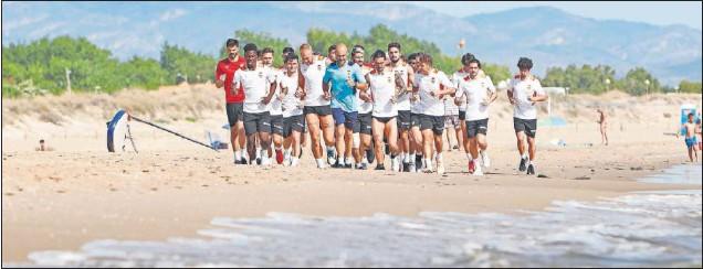 ??  ?? La plantilla del Valencia, entrenándose en la playa de Oliva.