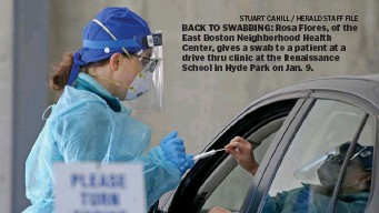 ?? sTuarT CaHill / Herald sTaff file ?? BACK TO SWABBING: Rosa Flores, of the East Boston Neighborhood Health Center, gives a swab to a patient at a drive thru clinic at the Renaissance School in Hyde Park on Jan. 9.