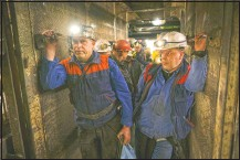 ??  ?? Miners hold bags of food as they stand in an elevator taking them underground.