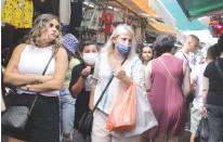 ?? (Marc Israel Sellem/The Jerusalem Post) ?? SHOPPERS WALK through Tel Aviv's Carmel Market yesterday.