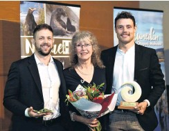 ?? PHOTO: GREGOR RICHARDSON ?? For the love of frogs . . . The family of the late Prof Phil Bishop, Wild Dunedin's Wild Hero for 2021, wife Debbie Bishop and sons Adam (left) and Luke, accept his award at the Otago Museum during Wild Dunedin's opening night celebratio­ns on Earth Day.