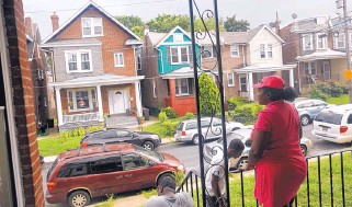 """?? PATRICK SEMANSKY/ASSOCIATED PRESS ?? Maria Williams stands on her front porch in Wilmington, Del., on July 27, 2017, the day after her teenage son and daughter were shot and wounded while standing on the same porch. As she took cover inside and heard her kids' screams, """"All I could think..."""