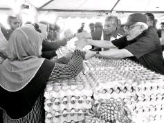 ?? - Bernama photo ?? Deputy Prime Minister Datuk Seri Dr Ahmad Zahid Hamidi attending to customers at the Jualan Sentuhan Rakyat in Bagan Datuk yesterday.
