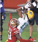 ?? GETTY IMAGES ?? Packers receiver Davante Adams makes a circus catch for a touchdown despite the efforts of Emmanuel Moseley in November.