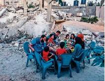 ?? AFP ?? ►GAZA. Una familia palestina desayuna cerca de las ruinas de su vivienda que fue destruida por los enfrentamientos.