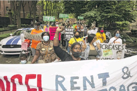 ?? ASHLEE REZIN GARCIA/SUN-TIMES ?? Protesters march to Gov. J.B. Pritzker's Gold Coast mansion on Tuesday urging cancellation of rent and mortgage payments.