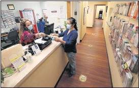 ?? ALEXA WELCH EDLUND/ TIMES-DISPATCH ?? Eleanor Sanchez, manager of CrossOver Healthcare Ministry's Richmond clinic, assists Sara Eunice Cruz. CrossOver is the largest charitable clinic in the Richmond area.