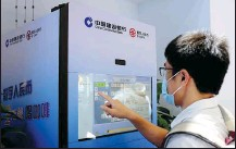 ?? REUTERS ?? A visitor uses a vending machine promoting e-CNY during the World Artificial Intelligence Conference in Shanghai.