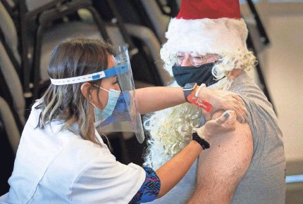 ?? ERNST PETERS/USA TODAY NETWORK ?? Florida Presbyterian Homes CEO Joe Xanthopoulos, dressed as Santa, receives a Pfizer COVID-19 vaccination from Walgreens pharmacist Ericka Gutierrez in Lakeland, Fla., on Dec. 22.