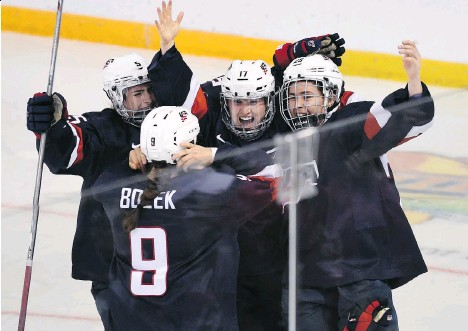 ?? RYAN REMIORZ/THE CANADIAN PRESS ?? U.S. players celebrate their 1-0 win over Canada in overtime in the gold medal game on Monday in Kamloops.