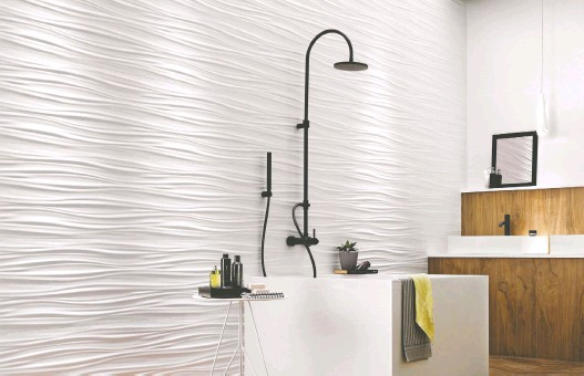 ?? PHOTOS COURTESY OF CIOT ?? A 3D wall of white ribbon design evokes waves and will brighten any bathroom. Below, a white diamond pattern results in an almost floral-looking textured design.