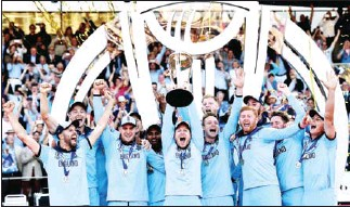 ?? AFP ?? England's captain Eoin Morgan lifts the World Cup trophy as England's players celebrate their win after the 2019 Cricket World Cup final against New Zealand on July 14, 2019.