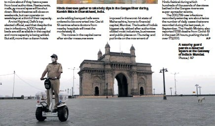 ?? Photos / AP ?? A security guard patrols a deserted square at the Gateway of India in Mumbai.