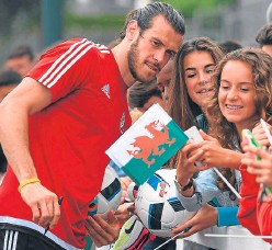 ?? Picture: Getty. ?? Wales' player Gareth Bale poses for selfies after an open training session at the Welsh base yesterday.