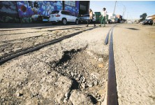 ?? Noah Berger / Special to The Chronicle ?? Pedestrians pass a pothole on 18th Street in Oakland. Voters OKd $600 million for infrastructure and affordable housing.