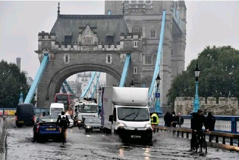?? (AFP/Getty) ?? Vehic l es strugg l e through f l ood waters at Tower Bridge yesterday