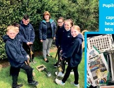 ??  ?? Pupils burying the time capsule with head teacher Mrs Williams