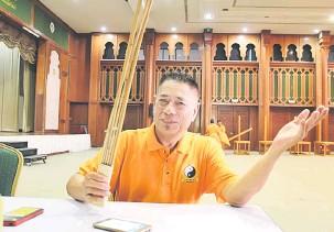 ??  ?? BERKESAN: Osman menunjukkan rotan yang digunakan dalam teknik Zai Mai iaitu pukulan pada badan untuk melancarkan peredaran darah.