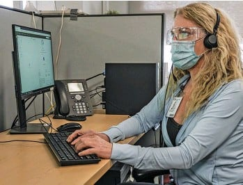 ?? SUPPLIED ?? An Access 24/7 staff member wearing PPE, working at her desk to provide care and support for a caller.