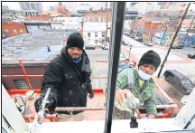 ?? JOE MAHONEY/TIMES-DISPATCH ?? Contractor­s Deonta Brandon (left) and Patrick Percywork on window casings on Masons'
