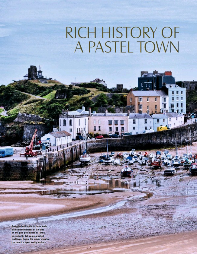 ??  ?? Snuggled within the harbour walls, boats sit motionless at low tide on the pale gold sands at Tenby, encircled by tall pastel-washed buildings. During the colder months, the beach is open to dog walkers.