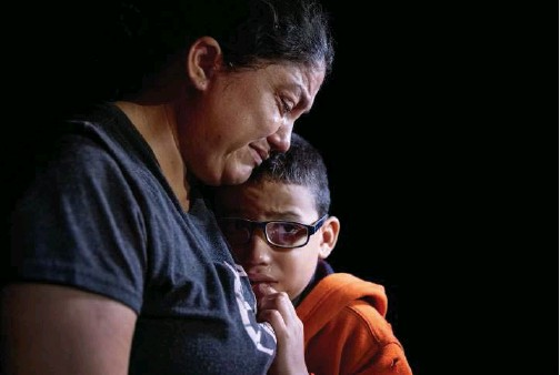 ?? Agence France-presse ?? An immigrant mother and son weep after completing their month-long journey from Honduras to the United States on Wednesday in Roma, Texas.