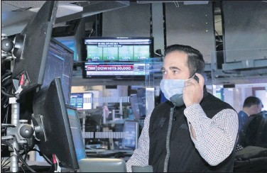 ?? NEWYORK STOCK EXCHANGE ?? A NewYork Stock Exchange traderworked at his terminal on Tuesday. The DowJones Industrial Average traded above 30,000 points for the first time on encouraging progress on coronavirus vaccines and the transition of power in the U.S.