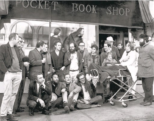 """?? Peter Breinig / The Chronicle 1965 ?? Poets gather in 1965 outside City Lights bookstore, which originally opened in 1953 as City Lights Pocket Book Shop in San Francisco. Back row: Stella Levy, Lawrence Ferlinghetti. Middle row: Donald Schenker, Michael Grieg, unknown person, Mike Gibbons, David Miltger, Michael McClure, Allen Ginsberg, Dan Langton, Steve Brostan, Gary Goodrow and son Homer, Richard Brautigan (in back of Goodrow). Front row: unknown person, Shigeyoshi """"Shig"""" Murao, Lew Welch, Peter Orlovsky."""